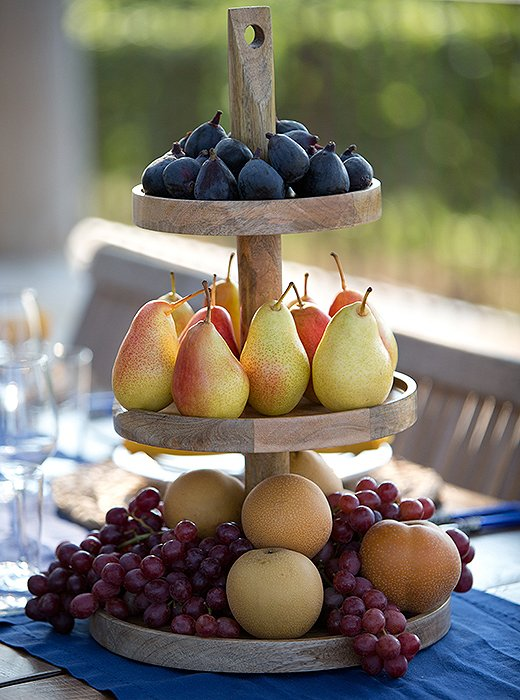 A tiered stand piled high with seasonal fruit pulls double-duty as decor and serving piece.