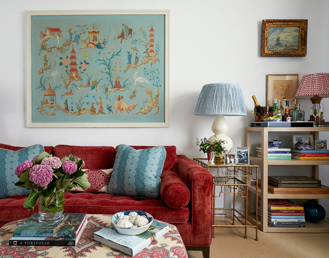 """Lilse originally planned to reupholster her red sofa, a holdover from a previous apartment. """"It was this tricky red to work with,"""" she says. """"But like all great design challenges it ended up producing what I think is an interesting scheme."""" She mixed in plenty of blues and greens to cool things off, and the large-scale artwork tied everything together in a stroke of serendipity: Her cousin had inherited it from their grandparents but,unable to find a spot for it, offered it to Lilse at the perfect moment. """"I had completely forgotten about this piece, and it fit perfectly,"""" she says. """"And it was the last thing to go in there!"""""""