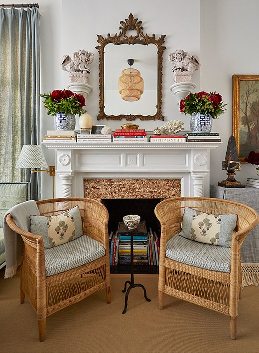 """The original fireplace, though no longer functioning, adds tons of historic character to the space. Lilse opted not to change the apartment's existing white paint job. """"The more we added fabric and artwork and furniture into the space, the more I really actually liked this chalky white,"""" she says. It makes a crisp canvas for artwork and antiques, plus """"it has a little texture to it."""""""