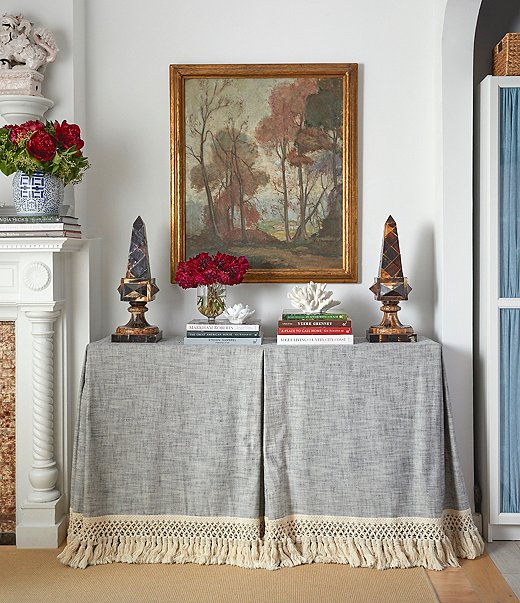 """The living room's elegant console (actually an Ikea table upgraded with a custom skirt) is a secret storage powerhouse, concealing bedding, towels, table linens, and off-season textiles. Books, objets, and a painting found at the Brimfield Antique Show make up an artful vignette on top, creating that layered feel that Lilse loves. """"My entire look veers toward lived-in and collected,"""" she says."""