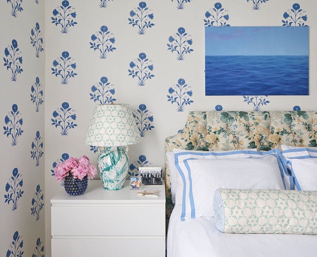 """When sourcing wallpaper for the bedroom, Lilse looked for a large-scale print with a lot of white space to highlight the 13-foot ceilings while keeping things airy. """"It's such a great space and you kind of lose that if you're not looking up, and your eye needs to be drawn up by something,"""" notes the designer. She landed on a block-print-inspired Les Indiennes print, which she paired with a classic Lee Jofa chintz headboard and a small-scale geometric accent fabric. Crisp white linens balance out the medley of patterns, while a seascape photograph adds a bold blue focal point."""