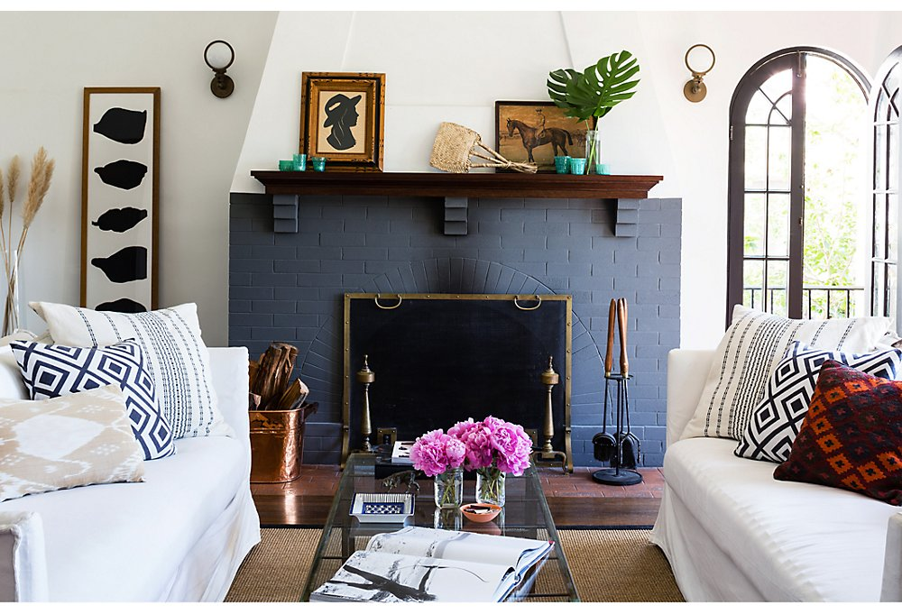 The painted brick fireplace is the focal point of the living room. Flanking it are Circa Lighting sconces Lizzie chose for their nautical form and vintage look.