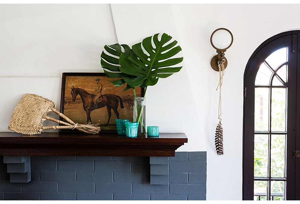 Lizzie keeps it low-key on the mantel with a jockey print from a Claremont, CA, antiques shop and palm fronds snipped from the yard.