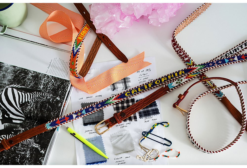 As Lizzie prepares to launch her ecommerce site, her desk fills with merchandise she's considering, from vintage souvenir belts to fabric swatches from a small Maine designer.