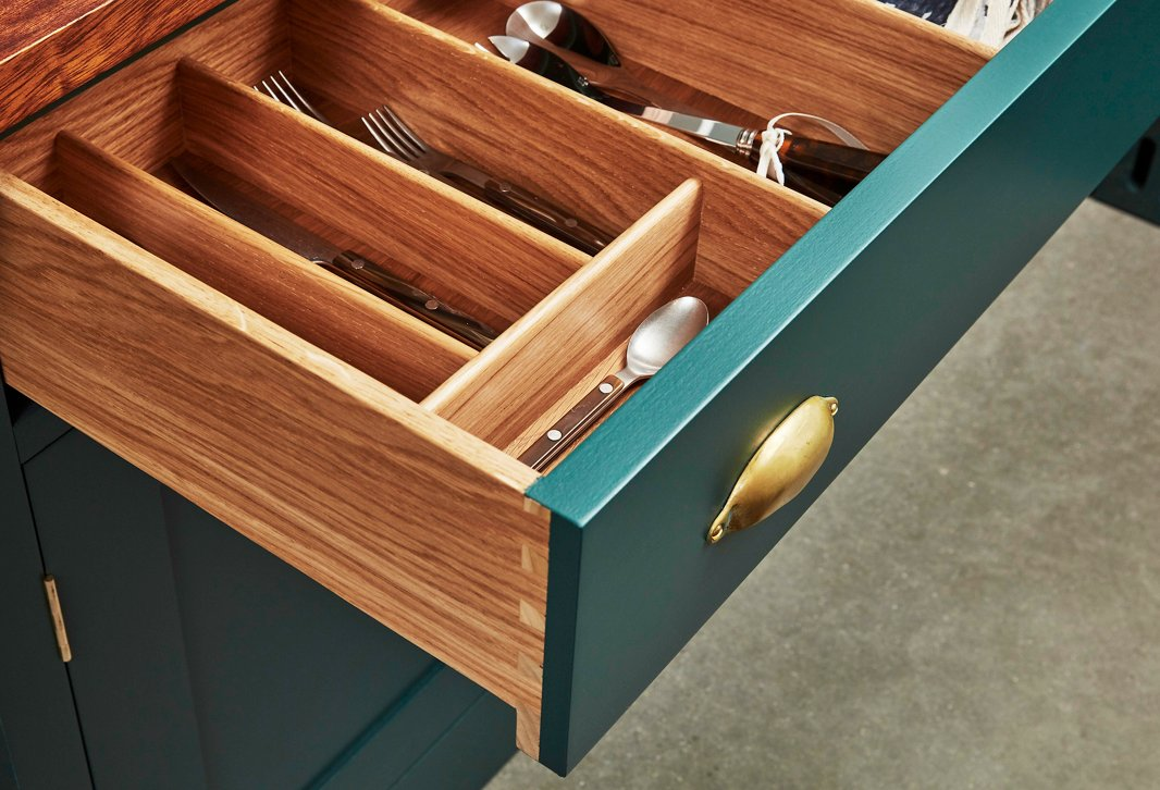 Dovetail joints, classic brass hardware, and hand-painted finishes give this Plain English kitchen a timeless feel. The divided drawer makes it easy to organize flatware and other kitchen accessories.
