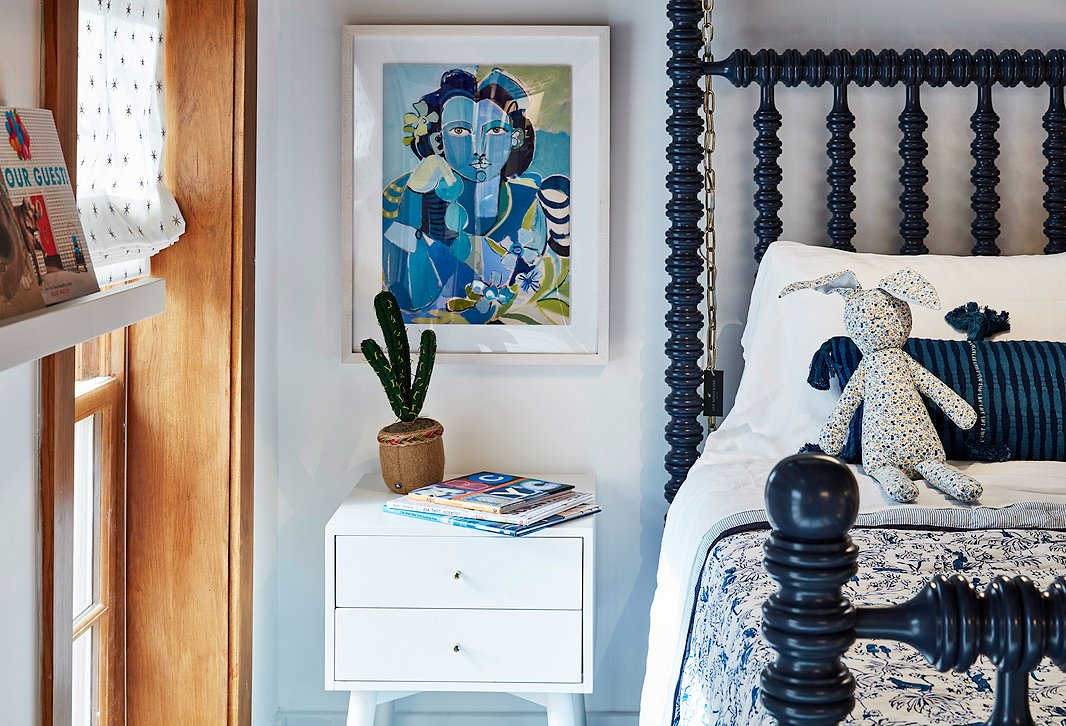 A cozy second-floor nook is home to an assortment of kids' furnishings, from pretty printed bedding to books and toys.