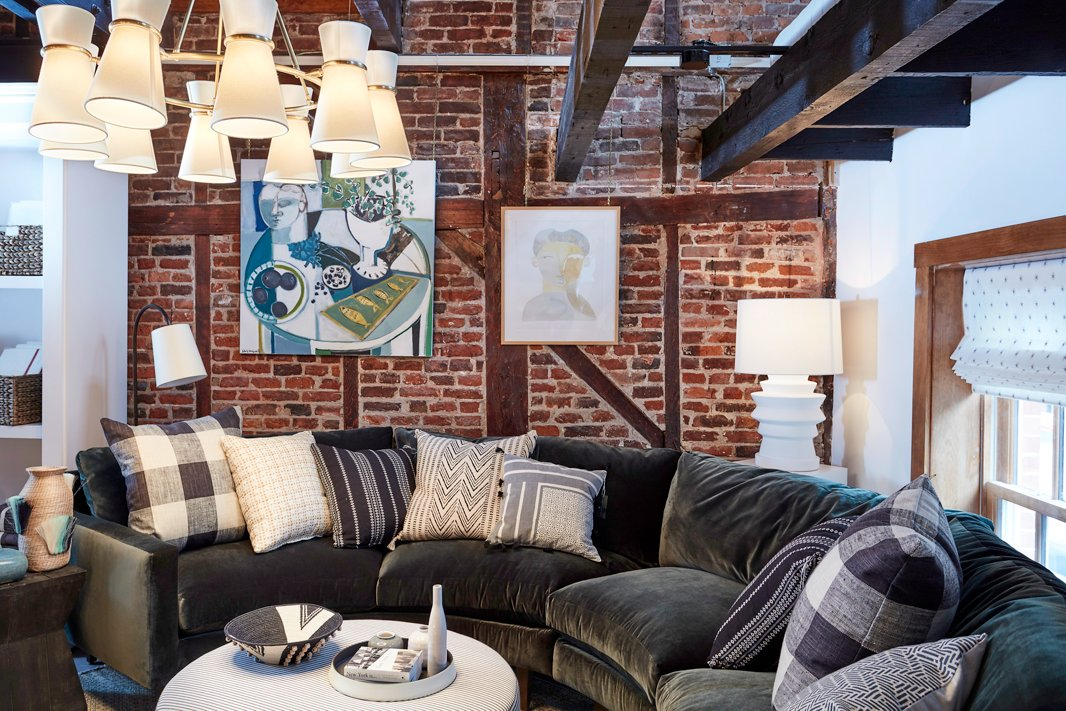 We love a curved sofa in a den or a living room. This one adds plush comfort to an upstairs lounge area in the shop, and the velvet upholstery contrasts beautifully with the exposed-brick wall.