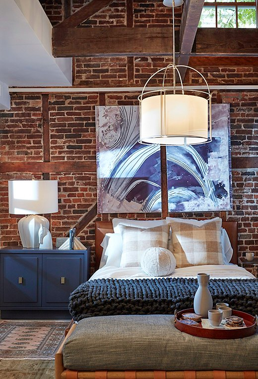 An oversize pendant light anchors the upstairs bedroom space.