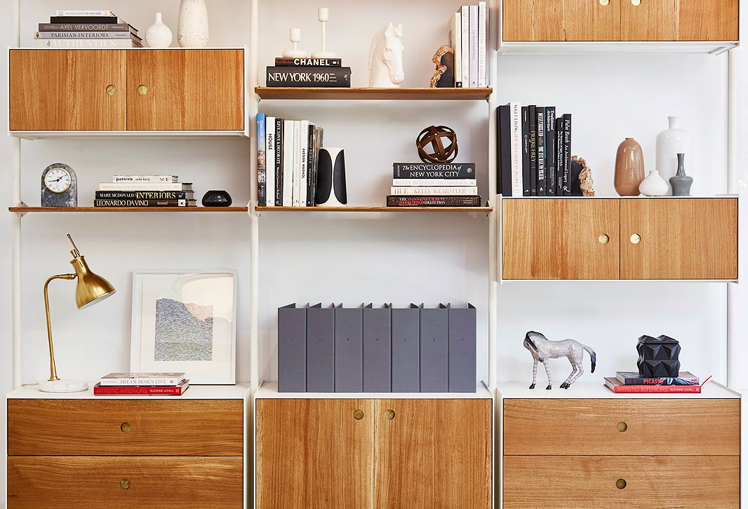 Midcentury-style shelves in the One Kings Lane Interior Design office house samples and supplies—plus a mix of books and ceramic objets.