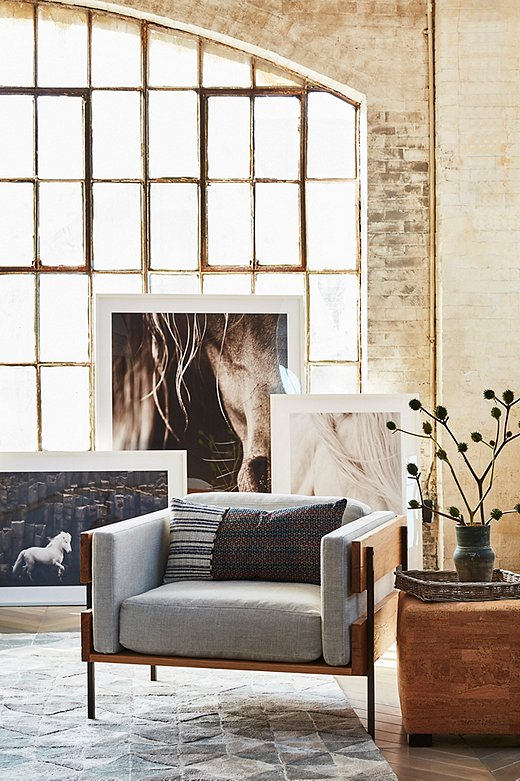 Minimalist silhouettes can often feel cold—but not when rendered in tactile linen and reclaimed oak, as with this club chair. Oversize equine photography plays up the rustic element; for a more cosmopolitan vibe, swap in abstract prints instead.