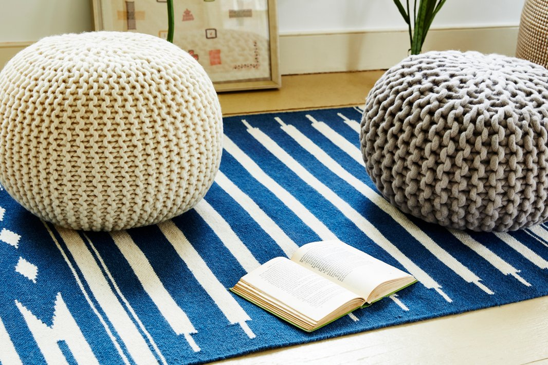 Top a soft flat-weave rug with a knit pouf or two to create a spot where everyone can get comfortable.