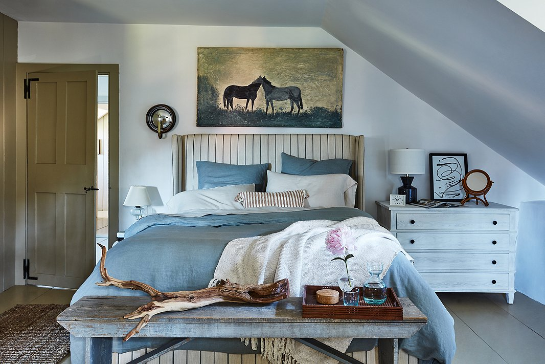 The classic combo of blue and white becomes warmer and more relaxed when softened by dashes of off-white (the striped tan bed, for instance). Seemingly nonchalant asymmetry adds to the laid-back look.