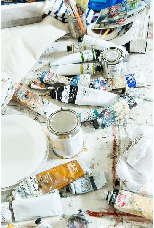 Tubes of paint and glass jars filled with brushes and tools cover a table in Mary's light-filled studio.