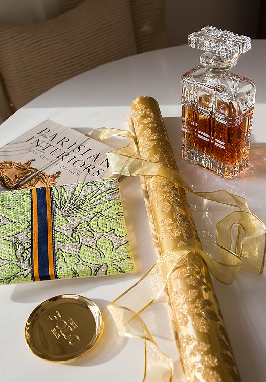 Ashley's One Kings Lane wish list includes (clockwise from top right): Ralph Lauren Home's Greenwich Decanter and Kipton Coaster, a punchy zippered pouch by Gaia, and a chic coffee table book.