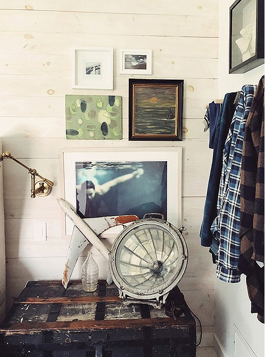 Next to the bed, a mixed-media gallery wall anchors a charmingly weathered vignette. A vintage trunk steps in as a side table (and adds welcome storage to the small space).