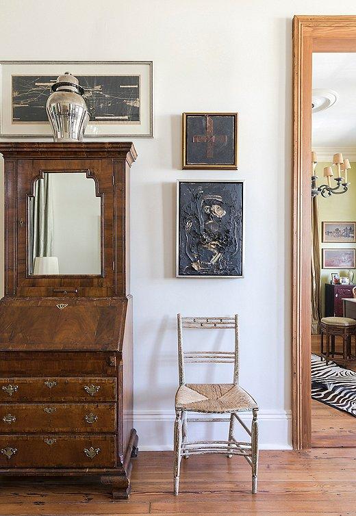 A trio of framed artworks around an antique secretary makes for an intriguing vignette.