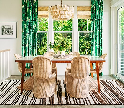 The dark brown stripes of the rug and the rich green leaf-motif curtain fabric set off the pale rattan chairs and tasseled light fixture perfectly. Photo bySeamus Peane, courtesy of designer Hannah Crowell.