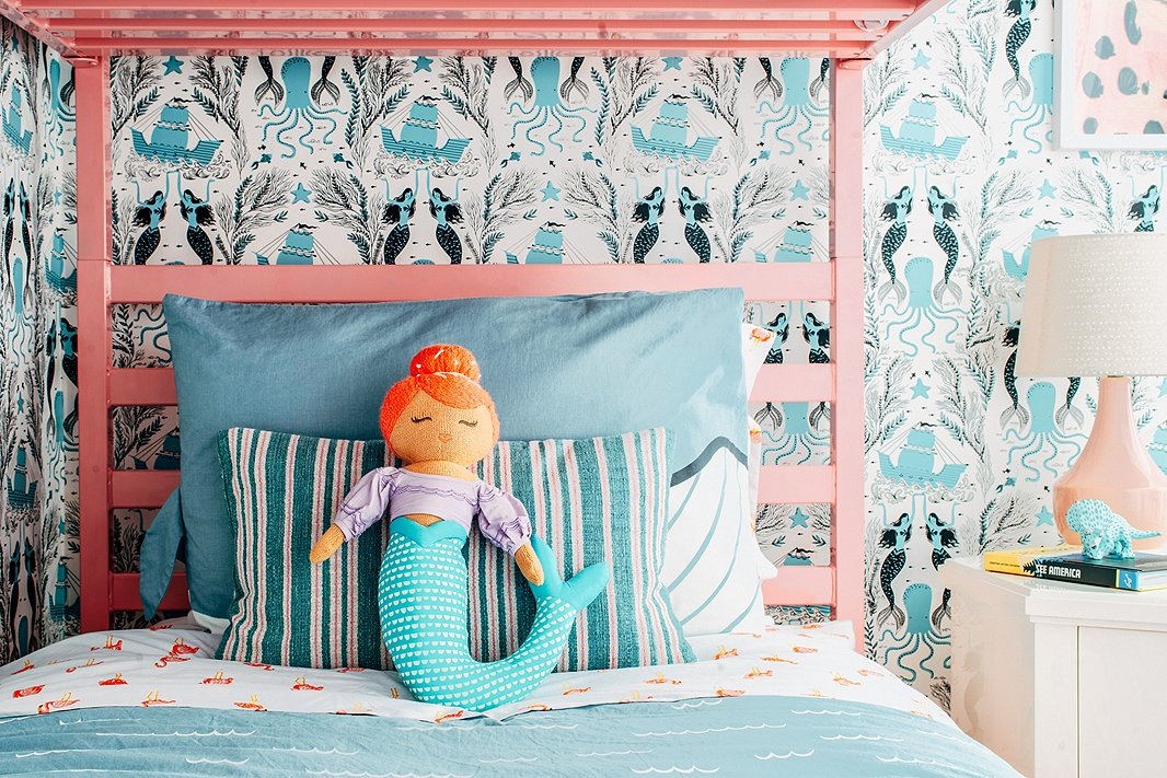 Flamingo-print sheets and mermaid-theme wallpaper offer playful nods to the home's Sunshine State setting—and when paired with classic stripes and timeless lighting, they manage to look more cute than kitsch.