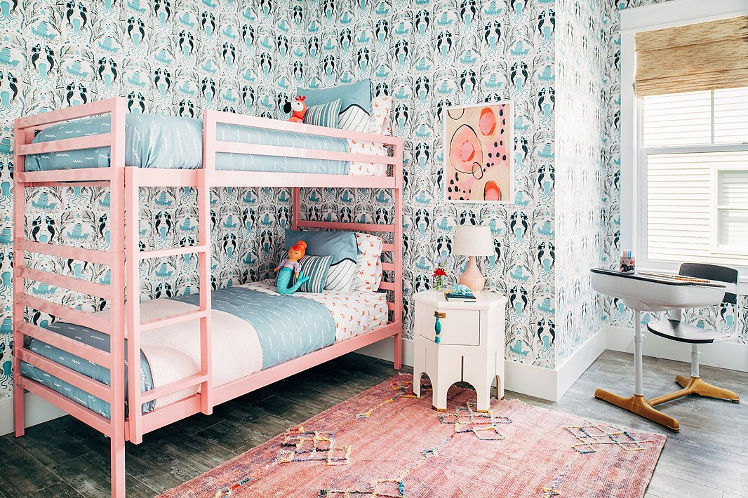 From the vintage rug to the Moroccan-inspired side table to the abstract artwork, this girls' room is anything but juvenile. The pink bunk bed? Pure fun.