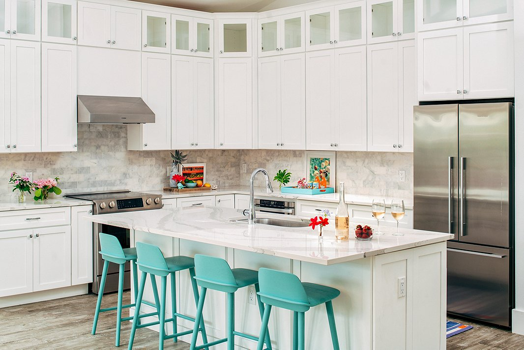 Light, bright, and airy: Everything you want in a beach-house kitchen. A row of turquoise barstools offers the perfect spot for post-pool lunch.