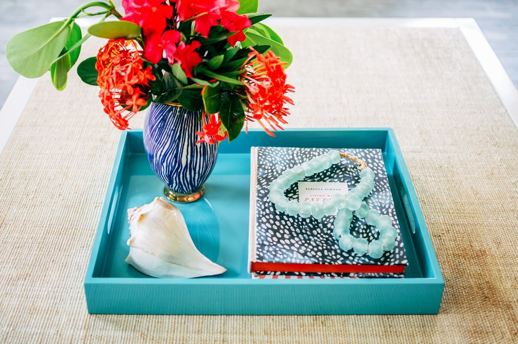 A string of beads in sea-glass blue and a vase of tropical flowers create a focal point atop the living room coffee table. The raffia surface adds relaxed, earthy texture to the space.