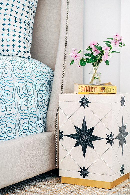 A side table with a black-and-white geometric pattern is an unexpected—yet decidedly chic—choice for a nightstand. The bed's neutral upholstery lets the blue-and-white linens take center stage.