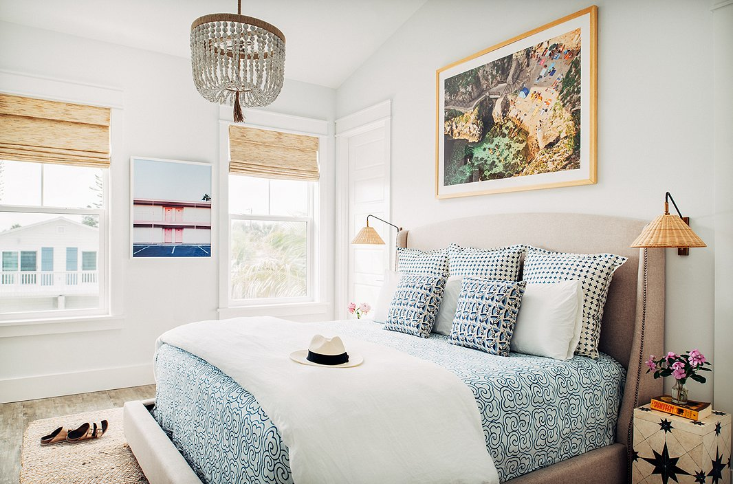"""I love mixing patterns and textures and prints,"" Hannah says—and she does so fearlessly, whether it's a bright banana-leaf fabric paired with a bold striped rug or a mix of three geometric prints on a bed, as in this master bedroom. ""I am of the mindset that if you love something, it will somehow work into the space."" For a similar chandelier, see the Surrey. The art on the far wall is Vegas Motel by Claudia Lucia."