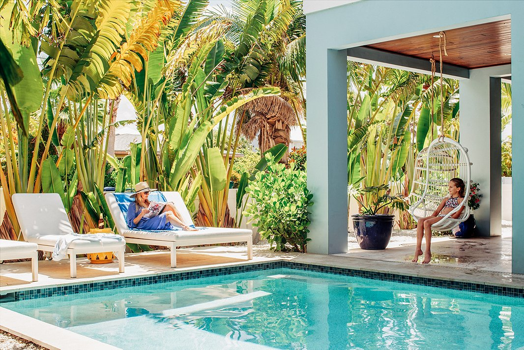 Towering palms, plush lounge chairs, and a seaside palette feel right at home on this Florida patio. Photo by Seamus Peane, courtesy of Hannah Crowell.