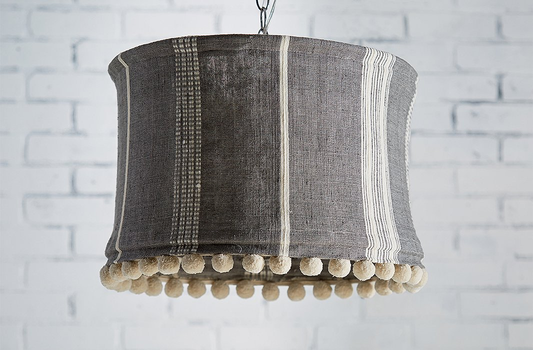 The Sutton Slipcover Pendant features a striped organic-cotton shade trimmed in cheerful pompoms. The fabric is hand-dyed and handwoven by skilled artisans in Ethiopia.