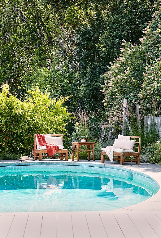 Weathered wood furnishings play up the wildness of the poolside landscaping. Photo by Laura Resen.