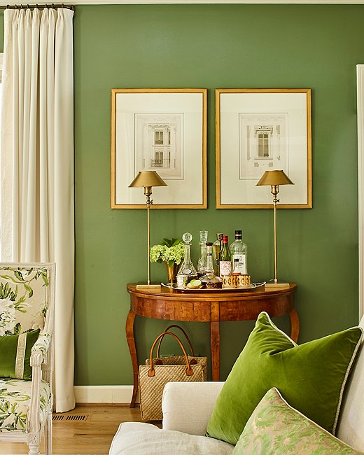 "Minnette craved a color that was ""rich but not overwhelming,"" and landed on this particular hue (Farrow & Ball's Calke Green) after seeing images of the green velvet-lined living room of designer Veere Grenney. Slim brass lamps (the Hayes table lamp by Chelsea House is similar) provide a cool counterpoint to an antique French demilune and a pair of French architectural engravings."