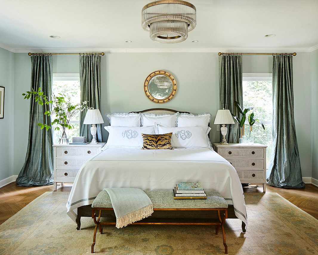 "Minnette designed the master bedroom to be a respite from the noise of everyday life, and chose a color palette of ""watery"" blues to create that restful atmosphere. A touch of Scalamandré tiger print pops against crisp and classic Matouk linens."