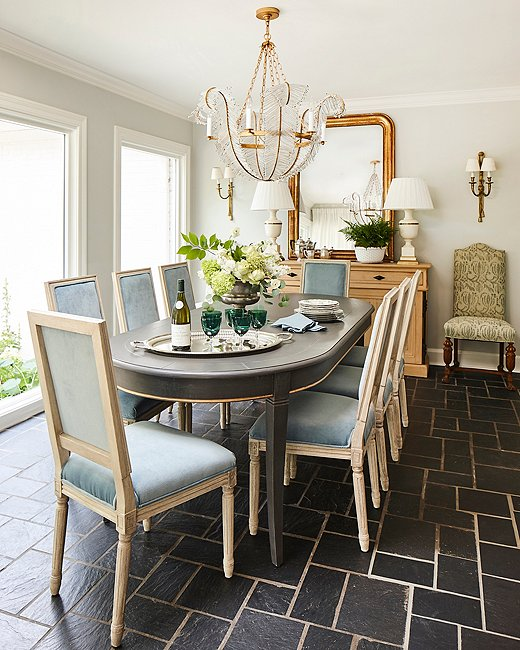 Floor-to-ceiling windows along one wall of the dining room help to bring the outdoors in. A Visual Comfort chandelier adds a touch of glamour and anchors the French Directoire-style table below.