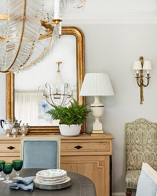 A large gold Louis Philippe mirror, a lucky French flea market find, leans casually atop the sideboard. Vintage sconces help create an inviting glow for evening gatherings.