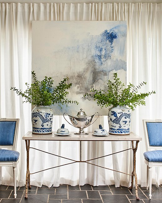 "A painting by Kelley Estes picks up on the dining room's cool blue color scheme. ""I love mixing contemporary and abstract art into interiors,"" says Minnette. ""The right piece can add a much-needed dose of color, form, and contrast that can keep a room from feeling too predictable or stuffy."""