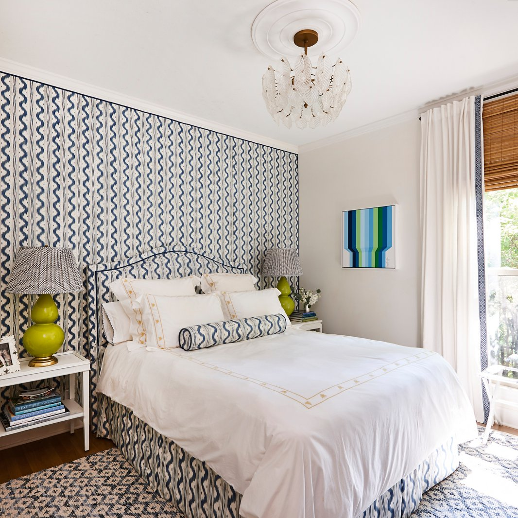 """""""I wanted to experiment in doing a room in an all-over pattern,"""" Minnette says, and the guest bedroom made the perfect candidate. Dressed in coordinating blue-and-white prints and accents of apple green, the space is now a dreamy home away from home. A op-art-style painting by Gina Julian adds a bold exclamation point."""