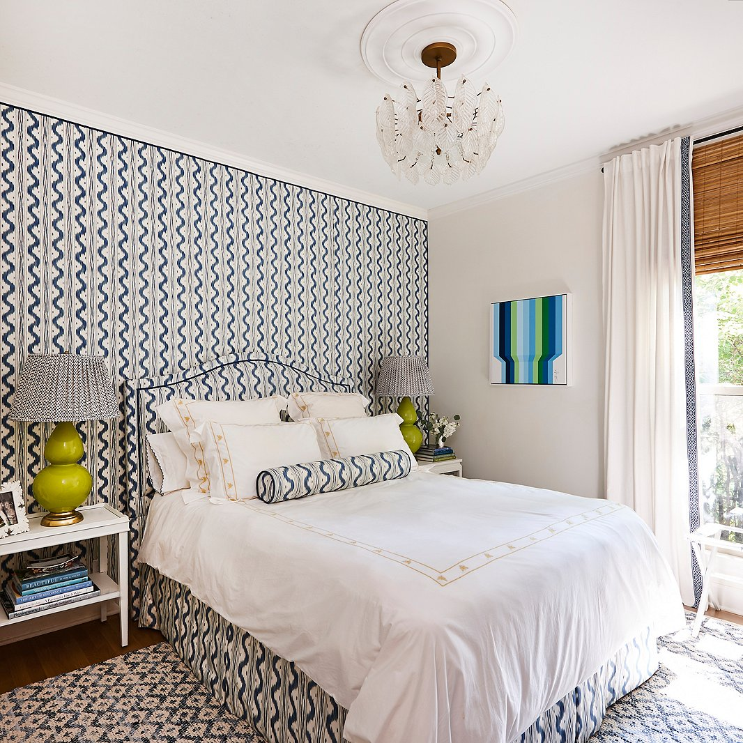 """I wanted to experiment in doing a room in an all-over pattern,"" Minnette says, and the guest bedroom made the perfect candidate. Dressed in coordinating blue-and-white prints and accents of apple green, the space is now a dreamy home away from home. A op-art-style painting by Gina Julian adds a bold exclamation point."