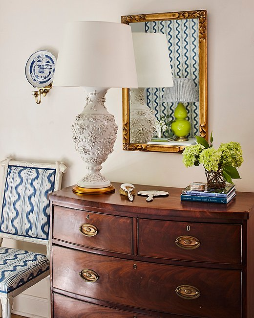 "A mirror handed down from Minnette's grandmother reflects the lively pattern on the opposite wall. The chest belonged to the designer's in-laws, and the lamp was an online auction score. ""We are lucky to have inherited several nice pieces from both of our families, and I am always collecting things I find pretty or interesting,"" Minnette says."