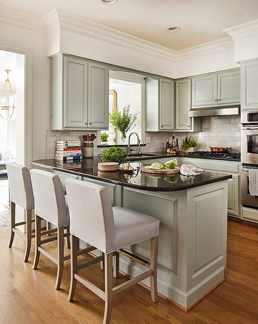 "While the kitchen didn't need a full reno, Minnette did give it a ""major facelift,"" ditching the faux adobe-textured walls for a crisp coat of white and painting the cabinets a pale sage green. She also replaced an ornate carving above the sink with a simple arch. The Shannon counter stools are similar to those shown above."