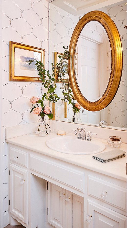 "Formerly a drab shade of brown, the petite powder room now features trellis-pattern wallpaper and a gold-framed mirror hung over the existing one. ""It's still small, but now it has a bit of a glam factor,"" Minnette says."