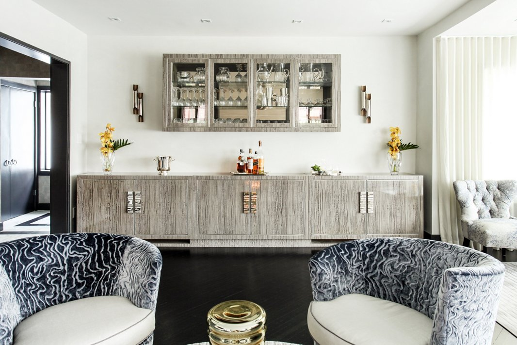 This custom bar is the home's entertaining command central. A coordinating wall-mounted cabinet provides extra storage and display space for Natalie's glassware collection.