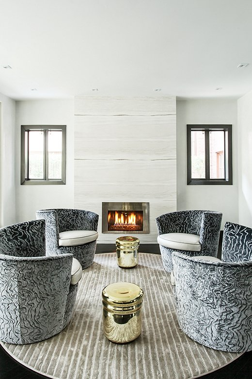 Natalie chose curvilinear pieces for the fireside seating area, including a round rug, metallic stools, and a set of swivel chairs (a favorite of Natalie's young kids), to counter the strong angles of the rest of the space.