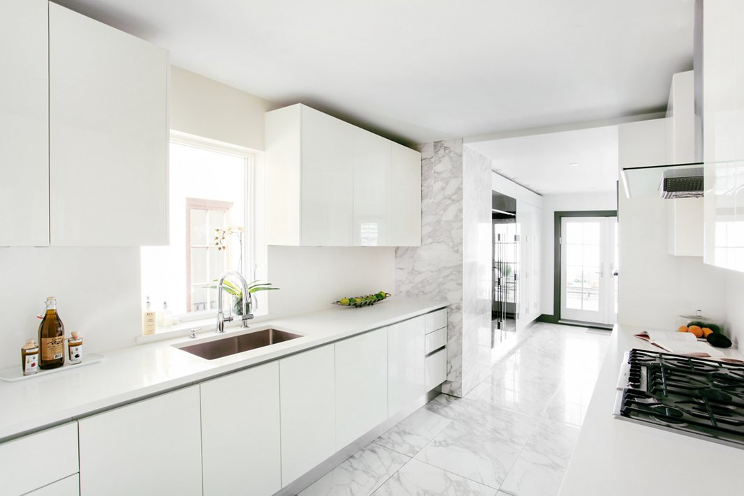 Sleek white surfaces and lots of closed storage keep this narrow kitchen from feeling cluttered. Post-renovation, the space opens onto a sunlit breakfast room, with French doors that lead to the patio.
