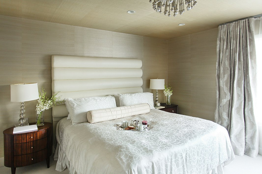 """I wanted to create a very soothing, calming space,"" says Natalie of the master bedroom. She brought the wallpaper up onto the ceiling to compensate for a lack of height; silky fabrics in a range of pearlescent beige tones enhance the jewel-box effect."