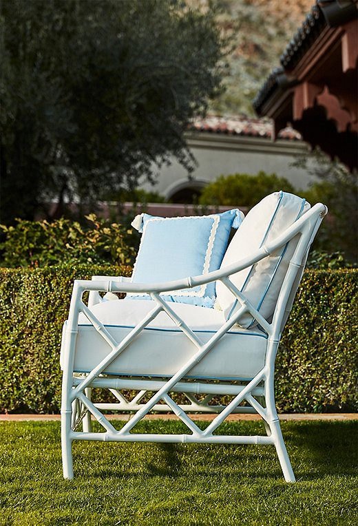 The Kit Lounge Chair (here in white) boasts a striking fretwork frame. We love it topped with the tasseled Liz Outdoor Pillow.