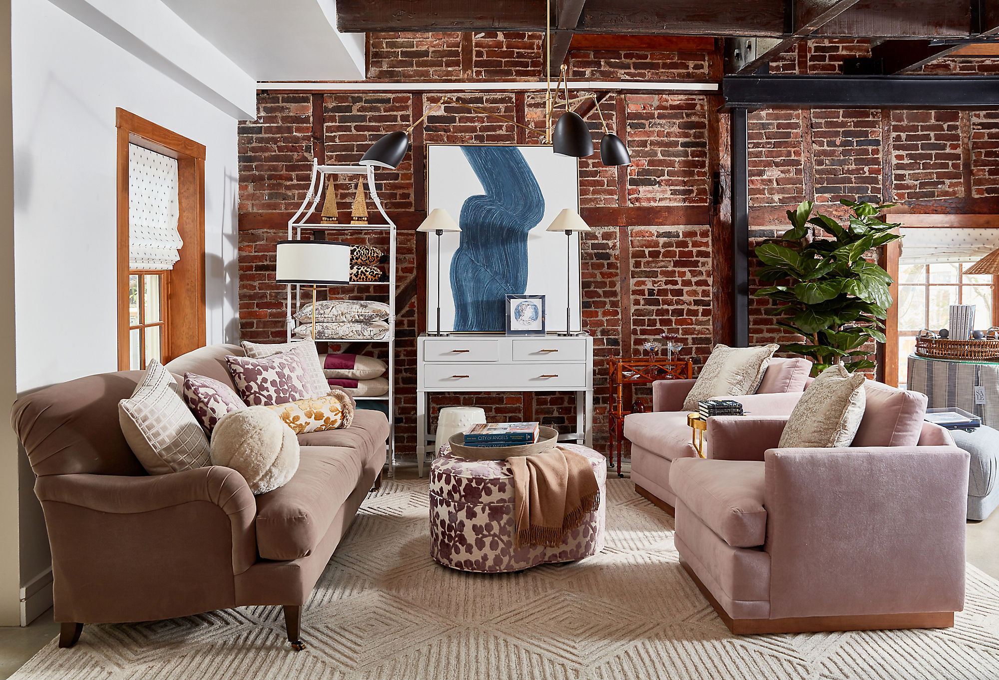 The sitting area features a pair of Shaw Swivel Club Chairs,aPortsmouth Upholstered Ottomanin amethyst-and-white velvet, and a cushy Hayes Sofa covered in stain-resistant Crypton velvet.