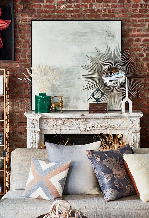 Abstract art atop the ornate mantel gives the eye a moment of rest. The Sunburst Mirror adds a touch of glam. This season is all about mixing modern and traditional aesthetics.
