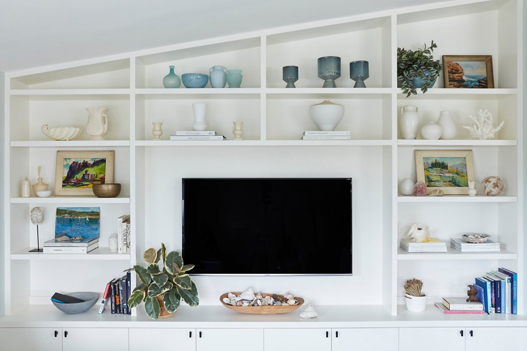 """Minnie added a wall of built-ins during the renovation process. To pull attention away from the TV, the One Kings Lane design team styled the shelves with a mix of new and vintage pieces, including coral and raw-wood accents and pottery in ocean hues. """"It softens the whole idea of a television,"""" Minnie says. """"It's made it into this really lovely space to look at."""""""