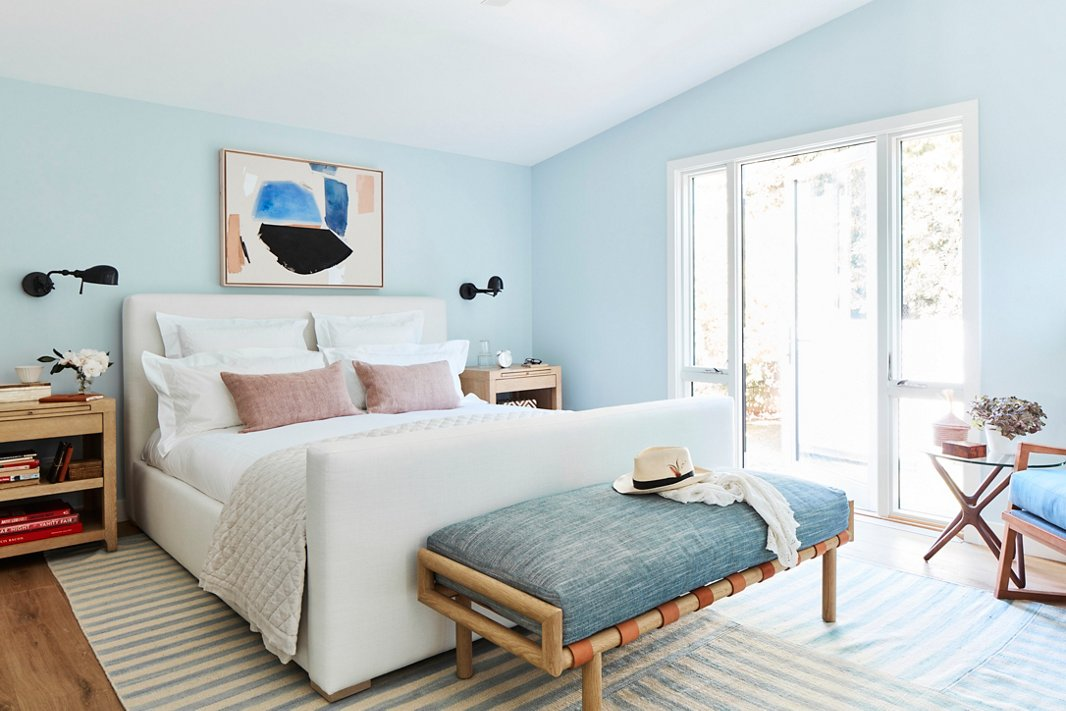 """""""I always love to have a bench at the end of my bed,"""" says Minnie, and this leather-strapped version by Community provides the perfect spot to toss decorative bed pillows or a robe while adding a touch of color and organic texture to the room. The upholstered bed, also by Community, meets Minnie's criteria of a """"statement bed"""" while aligning with the softly streamlined feel of the rest of the home."""