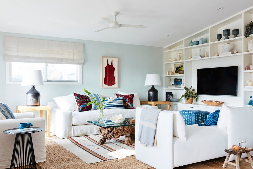 """Minnie's checklist for the living room seating: streamlined, white, slipcovered (see: sand), and deep enough to curl up on. """"I always feel like you want to be able to tuck your legs under you without your knees falling off the edge of the sofa,"""" she says. """"To me that's the mark of a great, comfortable family-living-space sofa."""" The striped rug and the bathing-suit artwork are vintage, the table lamps are by Ralph Lauren Home, and the window treatments are by The Shade Store."""